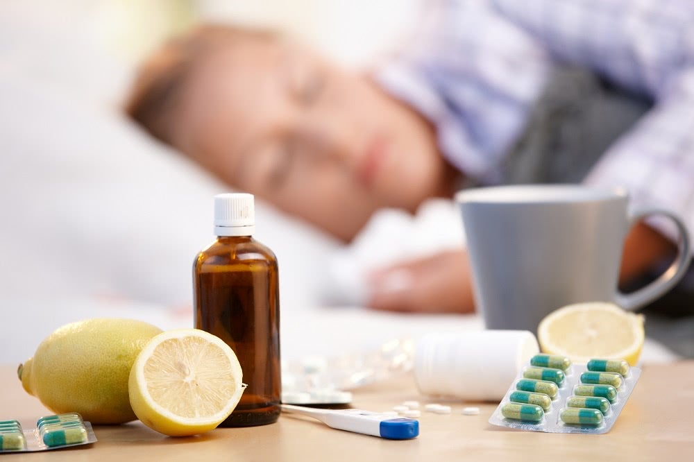 Woman Sleeping in Her Bed with Cold & Flu Remedies on Night Stand